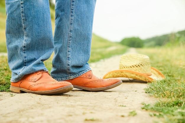 Ein cowboy beine in schuhen im park auf natur. der mann auf der ranch.