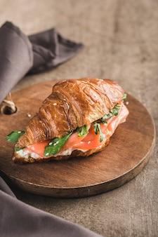 Ein croissant-sandwich mit lachs, ricotta und rucola auf einem holzbrett mit einer serviette