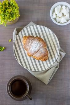 Ein croissant und kaffee auf einem grauen. die blumen. frühstück.