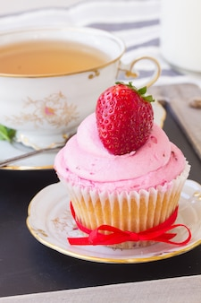 Ein cupcake mit frischer erdbeere in teller und tasse tee auf holztisch