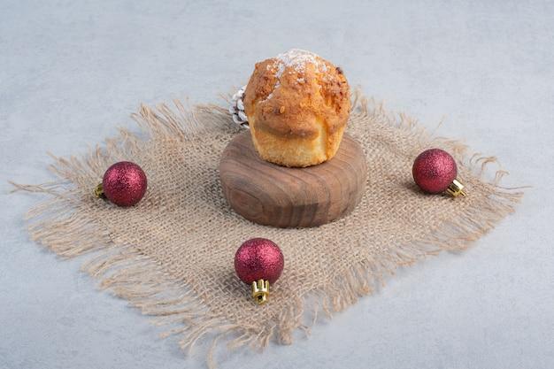 Ein cupcake und weihnachtsschmuck auf einem stück stoff auf marmoroberfläche