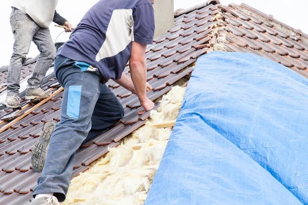 Ein dachdecker, der fliese auf das dach legt