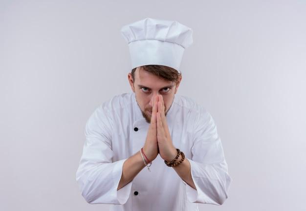 Ein dankbarer junger bärtiger kochmann in der weißen uniform, die hände in der geschätzten geste beim betrachten auf einer weißen wand hält