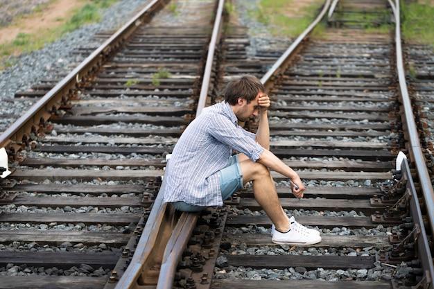 Ein depressiver mann, der auf den eisenbahnschienen sitzt und ein telefon in der hand hält, trifft eine schwierige entscheidung, in der vergangenheit zu leben oder seine zukunft zu ändern