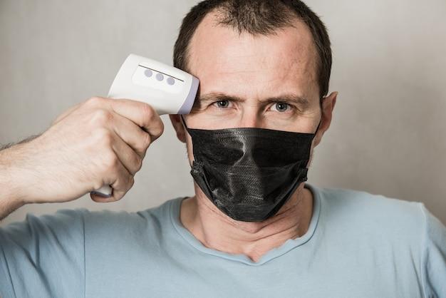 Ein depressiver mann, der eine schutzmaske trägt, die bereit ist, infrarot-stirnthermometer zu verwenden, um körpertemperatur auf virensymptome zu überprüfen - epidemisches virusausbruchkonzept. coronavirus.thermometerpistole