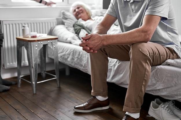 Ein depressiver mann sitzt in der nähe seiner kranken älteren frau und liegt krank im bett. im krankenhaus