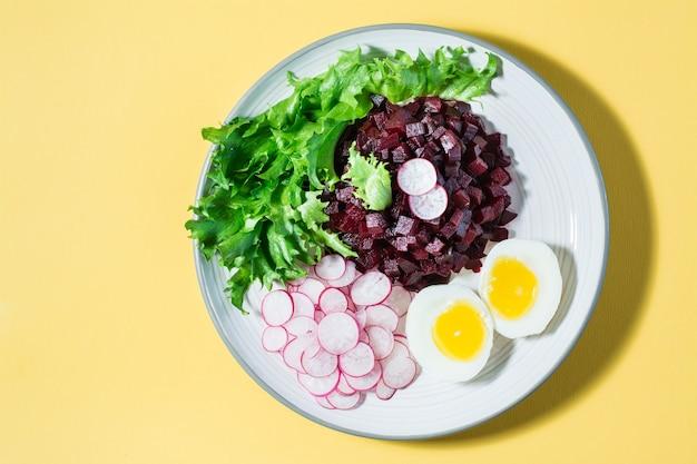 Ein diätetisches gericht aus gemüse. rübentatar, rettich, friessalat und gekochtes ei auf einem teller auf einem gelben tisch. ansicht von oben. platz kopieren