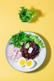 Ein diätetisches gericht aus gemüse. rübentatar, rettich, friessalat und gekochtes ei auf einem teller auf einem gelben tisch. ansicht von oben und vertikal
