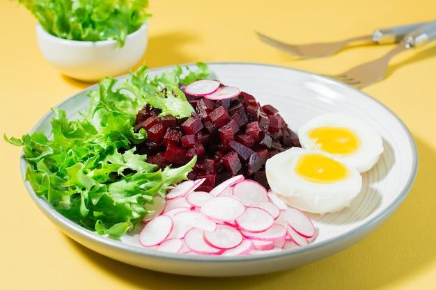 Ein diätetisches gericht aus gemüse. rübentatar, rettich, friessalat und gekochtes ei auf einem teller auf einem gelben tisch. hartes licht