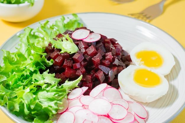 Ein diätetisches gericht aus gemüse. rübentatar, rettich, friessalat und gekochtes ei auf einem teller auf einem gelben tisch. nahansicht