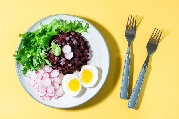 Ein diätetisches gericht aus gemüse. rübentatar, rettich, friessalat und gekochtes ei auf einem teller und einer gabel auf einem gelben tisch. direkt darüber