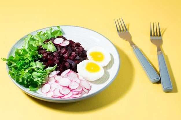 Ein diätetisches gericht aus gemüse. rübentatar, rettich, friessalat und gekochtes ei auf einem teller und einer gabel auf einem gelben tisch. hartes licht