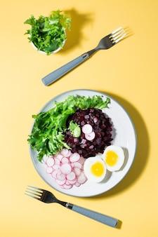 Ein diätetisches gericht aus gemüse. rübentatar, rettich, friessalat und gekochtes ei auf einem teller und einer gabel auf einem gelben tisch. vertikal- und draufsicht