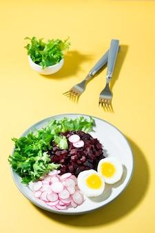 Ein diätetisches gericht aus gemüse. rübentatar, rettich, friessalat und gekochtes ei auf einem teller und einer gabel auf einem gelben tisch. vertikale ansicht
