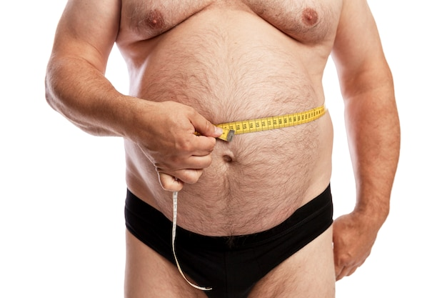 Ein dicker mann in kurzen hosen misst das volumen des bauches. isoliert. nahansicht.