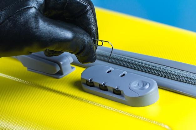 Ein dieb, ein betrüger versucht, ein zahlenschloss an einem koffer zu öffnen. diebstahl-konzept