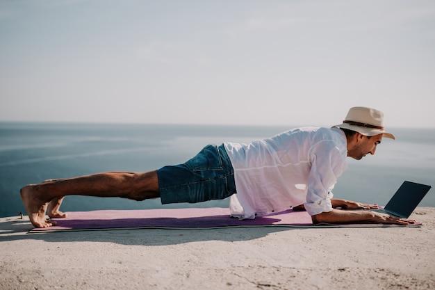 Ein digitaler nomade, ein mann mit hut, ein geschäftsmann mit einem laptop macht yoga auf den felsen am meer bei