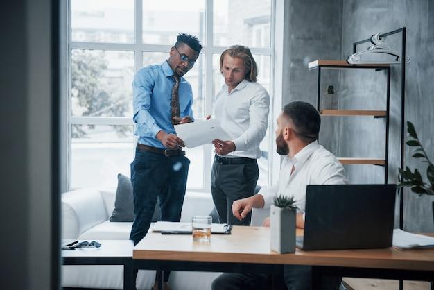 Ein dokument lesen. drei anzug tragen arbeiter, die zeit damit verbringen, berichte zu erstellen