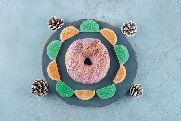 Ein donut, marmeladen und tannenzapfen auf marmor.