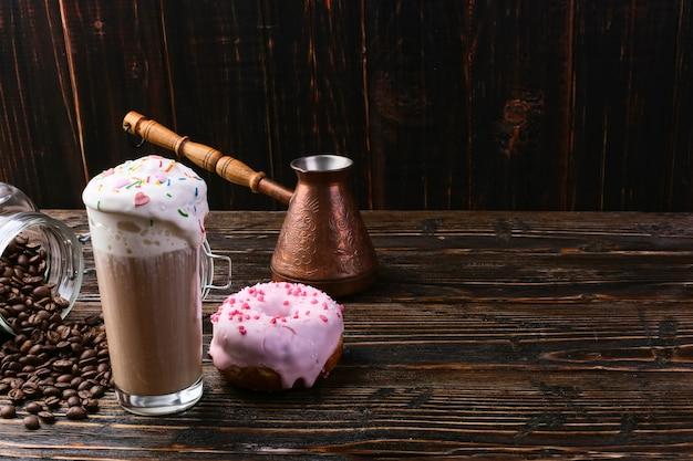 Ein donut mit rosa zuckerguss und schokoladenpulver und ein cappuccino-glas mit hohem schaum und dekoration. eine dose kaffee und körner einschenken.