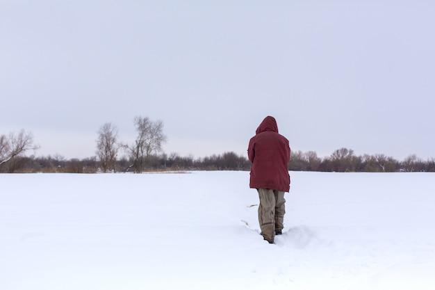 Ein dorfmann geht im winter auf dem gebiet