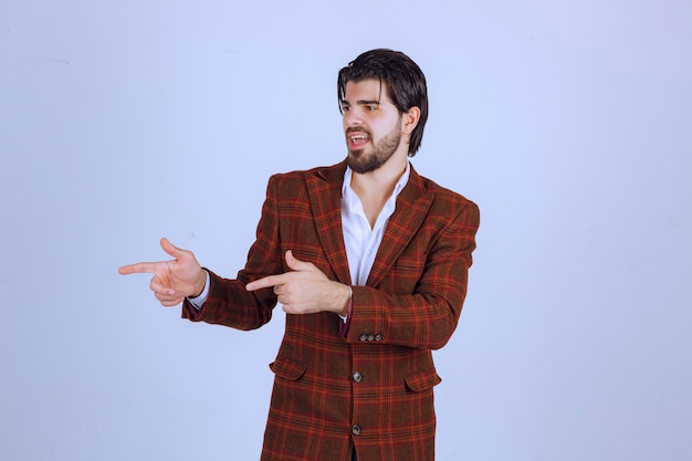 Ein dozent in braunem blazer zeigt nach links und spricht mit emotionen darüber.