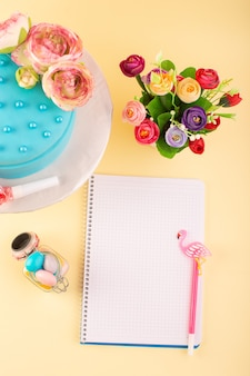 Ein draufsicht-heft und kuchen mit blumen auf der gelben schreibtischkuchengeburtstagsfeierfarbe