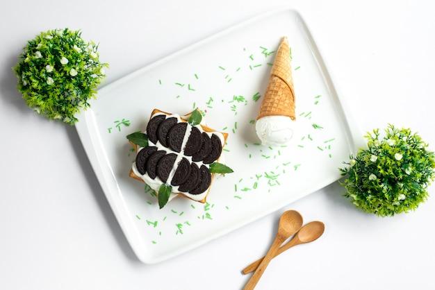 Ein draufsicht-keksdessert mit schokoladen-biscutis-vanillepudding, verziert mit blättern und eiscreme innerhalb des weißen schreibtisches auf der süßen sommer-süßwaren des weißen hintergrunds