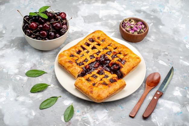 Ein draufsicht köstlicher erdbeerkuchen mit erdbeergelee-kirschen auf dem leichten schreibtischkuchen-kekszucker