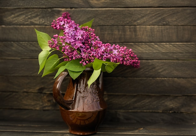 Ein duftender blumenstrauß aus flieder steht in einem kleinen rosa krug auf einem hölzernen hintergrund in einem rustikalen stil.