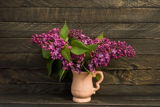 Ein duftender blumenstrauß aus flieder steht in einem kleinen rosa krug auf einer holzwand im rustikalen stil.
