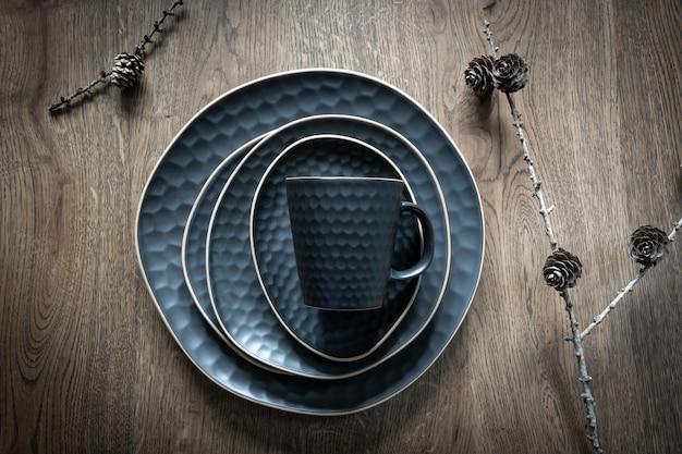 Ein dunkelblaues geschirr: eine tasse, eine untertasse, ein teller, eine schüssel und trockene lärchenkegel auf zweigen auf holzhintergrund. weihnachtstischdekoration, magische feiertage. ansicht von oben.