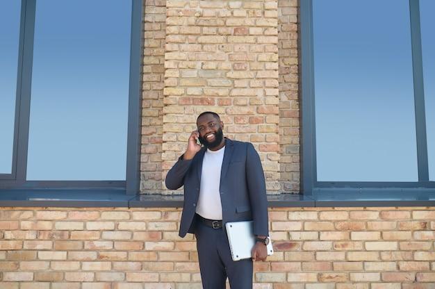 Ein dunkelhäutiger mann, der telefoniert und interessiert aussieht