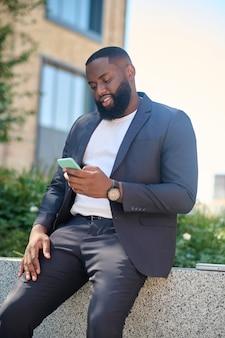 Ein dunkelhäutiger mann im anzug mit einem telefon in der hand