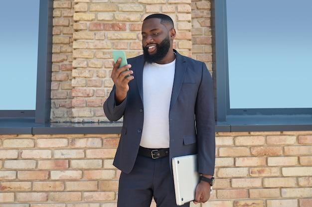 Ein dunkelhäutiger mann steht mit einem telefon in der hand