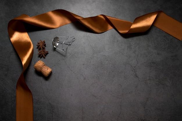 Ein dunkler hintergrund mit goldband, gewürzkorken-champagner und muzlet mit platz für ihren text.