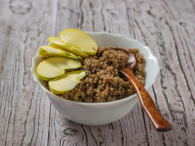 Ein dunkler holzlöffel und apfelscheiben in einer schüssel mit quinoa- und kakaobrei. gesunde ernährung.