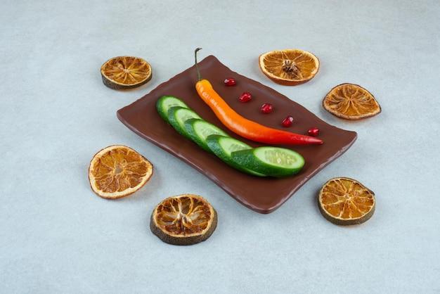Ein dunkler teller mit geschnittener gurke und chili-pfeffer.