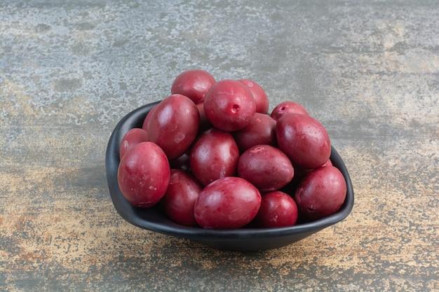 Ein dunkler teller mit köstlichen früchten auf weißem hintergrund. foto in hoher qualität
