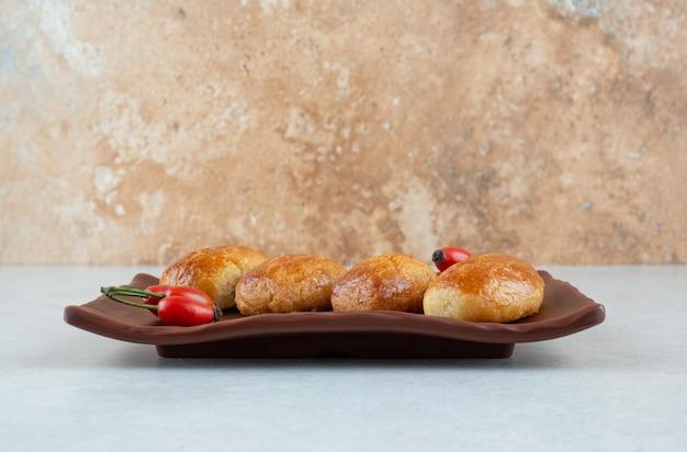 Ein dunkler teller mit süßen leckeren keksen mit hagebutten.