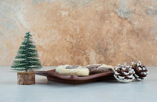 Ein dunkler teller mit zwei köstlichen keksen mit tannenzapfen und weihnachtsbaum.