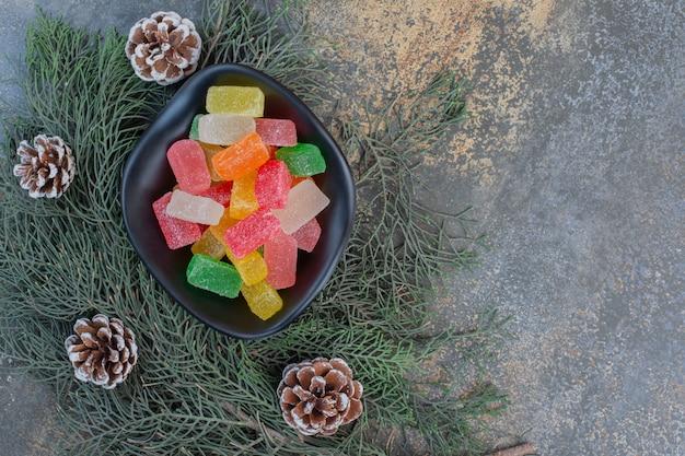 Ein dunkler teller voller süßer fruchtgelee-bonbons und tannenzapfen. hochwertiges foto