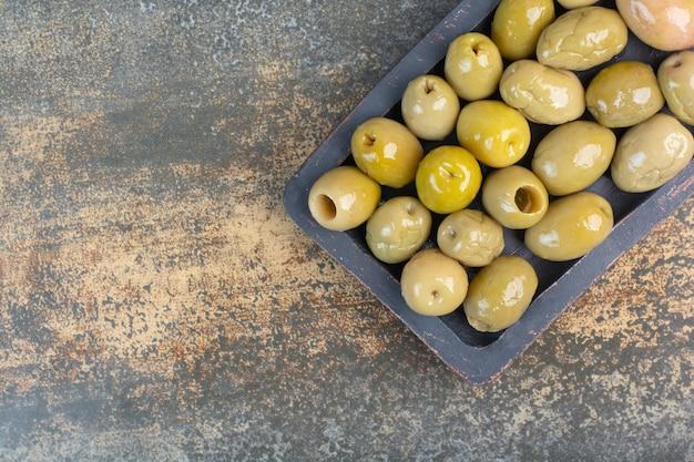 Ein dunkles brett einiger salziger köstlicher oliven auf marmorhintergrund