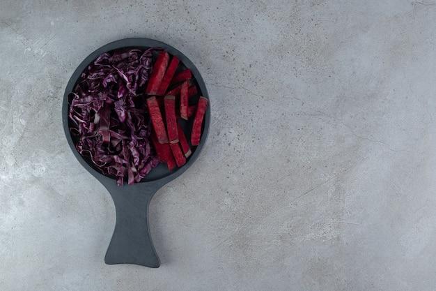 Ein dunkles brett mit geschnittenem kohl und roter beete. foto in hoher qualität