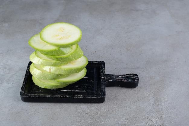 Ein dunkles brett mit geschnittener zucchini auf grauem hintergrund. foto in hoher qualität