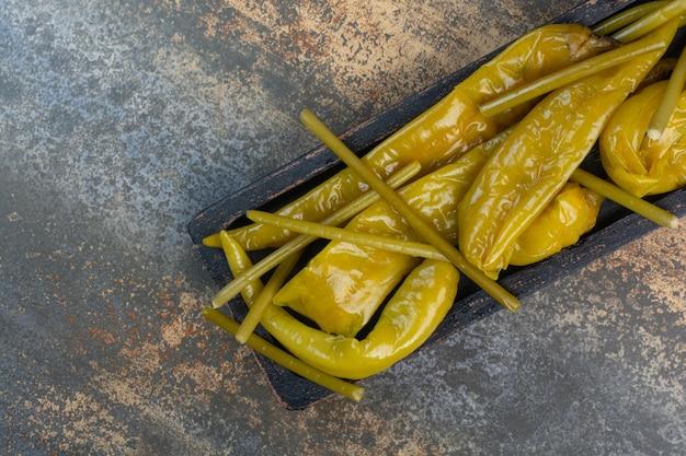 Ein dunkles brett voller salziger schmackhafter paprika auf marmorhintergrund. foto in hoher qualität