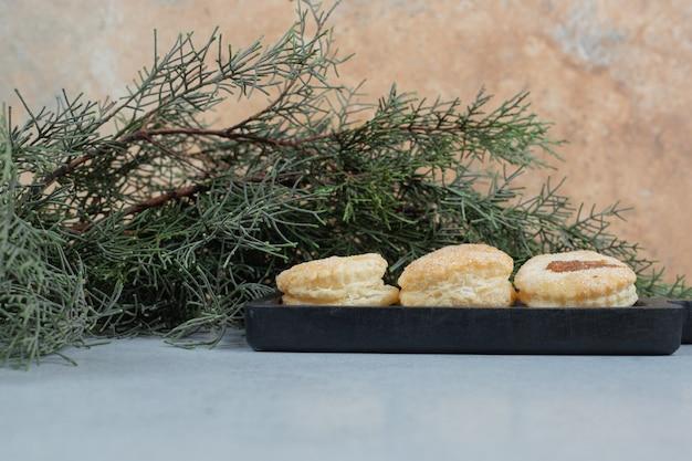 Ein dunkles brett voller süßer frischer runder kekse