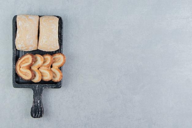Ein dunkles holzbrett mit süßen herzförmigen keksen.