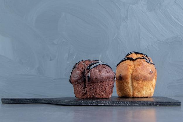 Ein dunkles holzbrett mit zwei süßen muffins