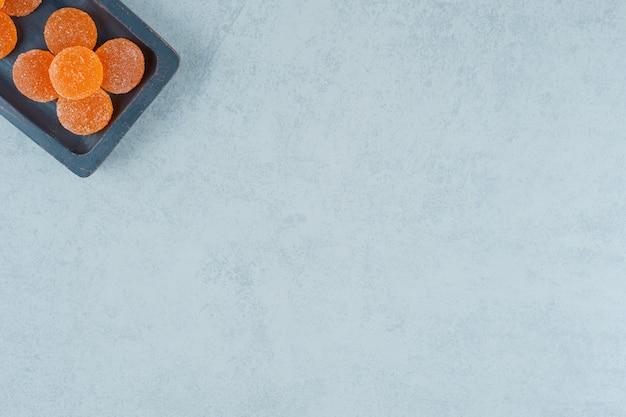 Ein dunkles holzbrett voller süßer orangengeleebonbons auf einer weißen oberfläche white
